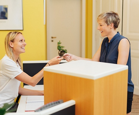 A dental receptionist accepting the card of a female patient who is paying for treatment