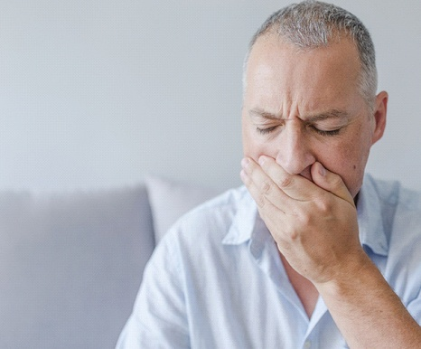 An older gentleman sitting on a couch and covering his mouth because of a soft tissue injury