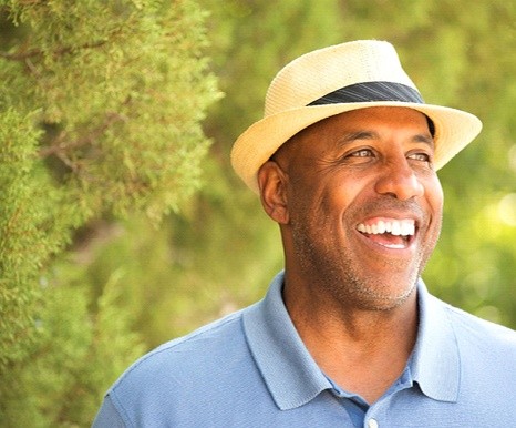 man in blue shirt and fedora smiling among trees