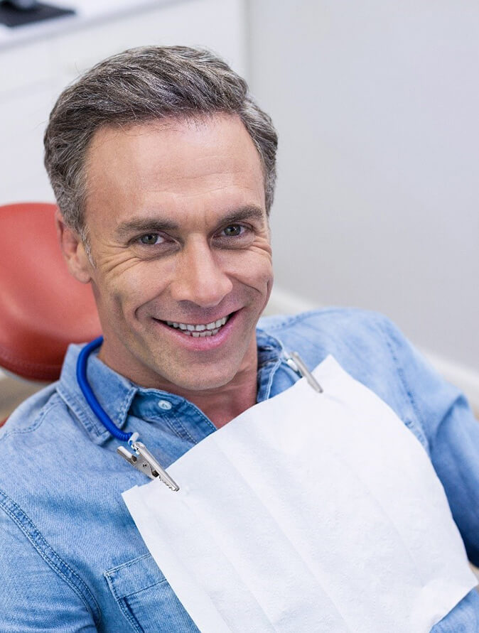 A middle-aged man seeing his dentist as part of his routine for the aftercare of dental implants in Spring