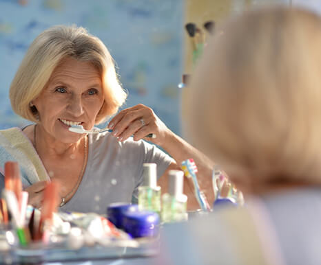 An older woman wearing a gray t-shirt and brushing her teeth and dental implants