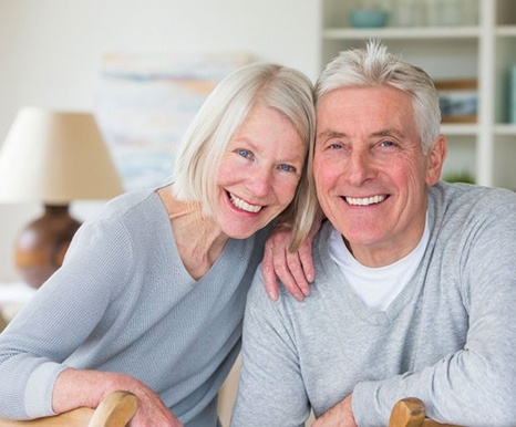older couple in gray sweaters smiling with dental implants in Spring