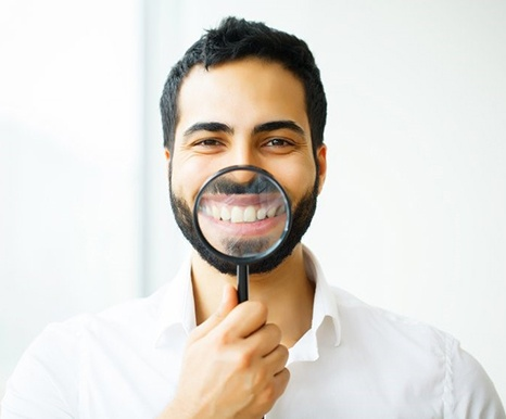 man in white dress shirt holding magnifying glass to his smile