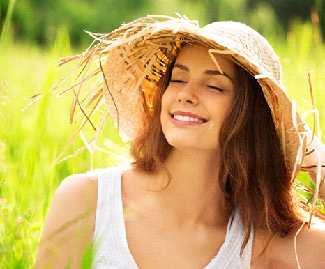 woman in sunhat with dental implant replacement teeth smiling outside