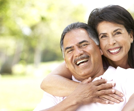 older couple with dental implant tooth replacement smiling hugging