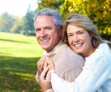 An older couple with dental implant replacement teeth smiling outside.