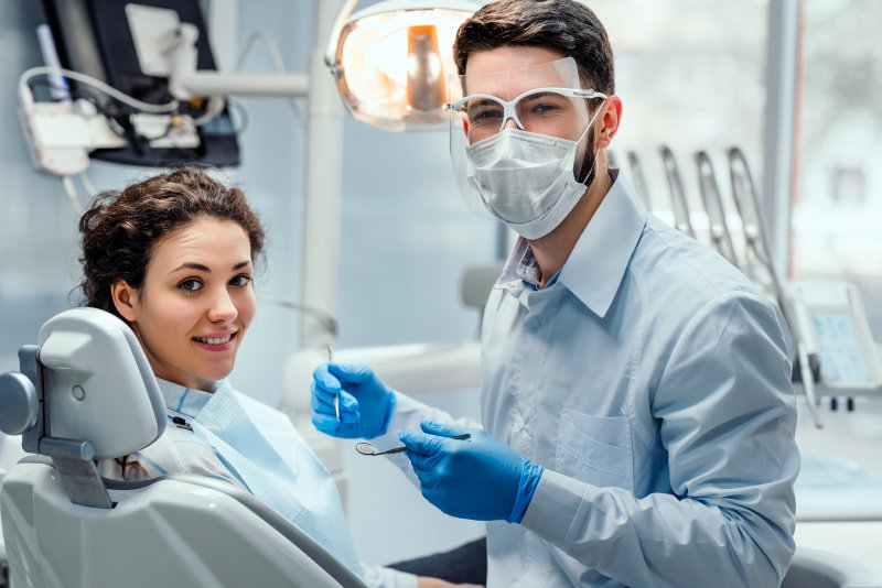 a dentist wearing PPE while preparing to assist a female patient in need of dental care