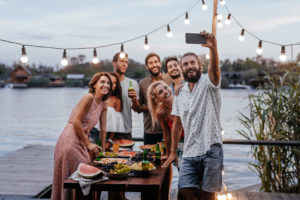 Group of young people taking selfie at outdoor party